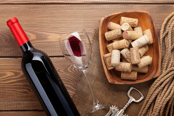 Red wine bottle, glass of wine, bowl with corks and corkscrew