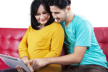 Expectant mother with husband using tablet