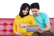Expectant woman with husband using tablet