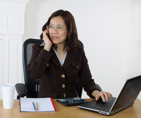 Mature business woman communicating on cell phone while at work