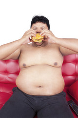 Fat person eating burger on sofa