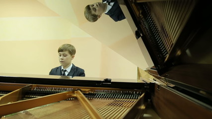 Boy playing the grand piano in the hall of the music school, pia
