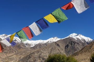 snow mountain range and tibetan prayer flags in the village