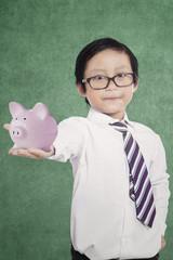Little boy showing moneybox