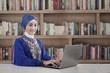 Muslim student working at library