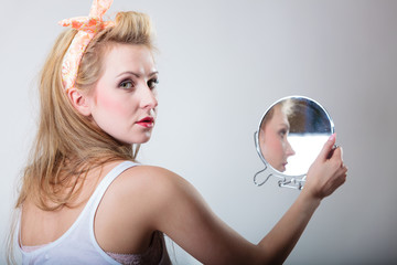 Pin up blonde fashion girl looking at mirror