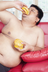 Overweight person eating two burgers at home