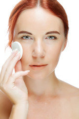 young woman applying a creme on her face