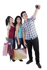Teenagers with shopping bags taking pictures