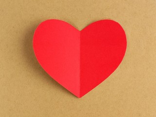 Red Valentines Day heart against a brown paper background