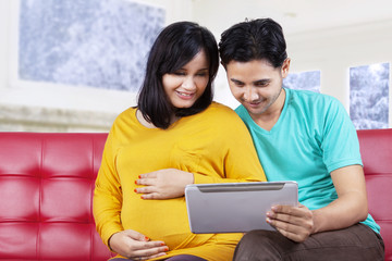 Young husband using tablet with his wife