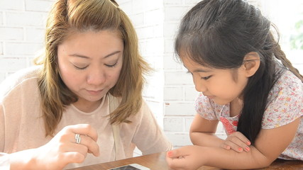 Asian Mother and daughter playing with electronic phone
