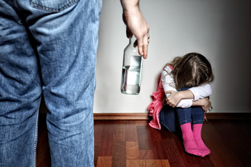 Father with belt stands above the frightened daughter