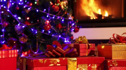 Closeup of Christmas gifts with fireplace in the background
