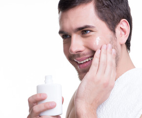 Young happy man applying cream.