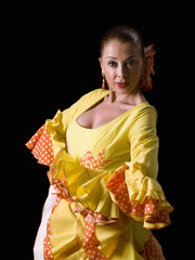 Spanish woman, dressed in flamenco, looking at the camera