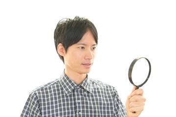 拡大鏡を持つ男性