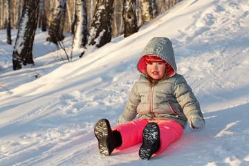 A little girl sliding down a hill