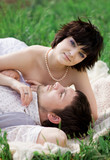 Young tenderness couple relax in blossoming garden poster