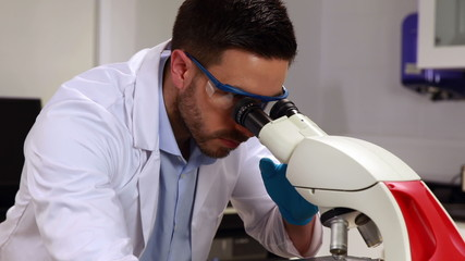 Young scientist looking through microscope in the lab