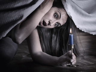 A young woman with fear, looking under the bed