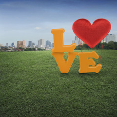 Love word with heart shape ballon on green grass field and offic