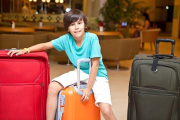 Мальчик с чемоданами в помещении