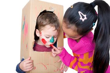 Kinder spielen mit einem Karton