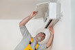 Electrician worker examine or install air condition in room