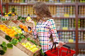 Девушка с корзиной в магазине продуктов
