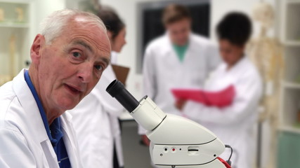 Medical professor looking through microscope