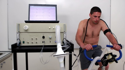 Fit man doing a stress test on exercise bike