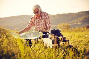 Wanderer sitzend mit Karte und Sonnenuntergang