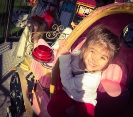 Bimba che gioca e sorride su una giostra