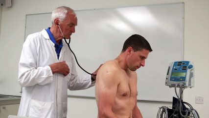 Doctor listening to patient with stethoscope