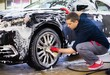 Man worker washing car's alloy wheels on a car wash - 75929445