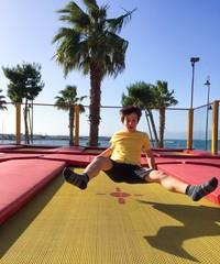 Bambino che gioca e salta su tappeto elastico