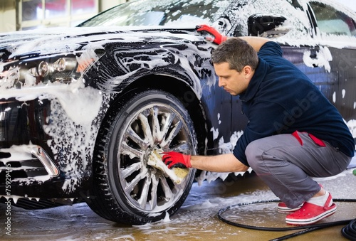 Leinwanddruck Bild Man worker washing car's alloy wheels on a car wash
