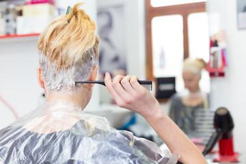 Hairdresser salon. Woman during hair dye.