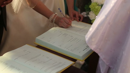 european bride in wedding dress make note in church book about m