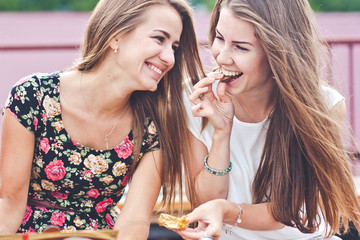 Two young females talk and laugh while eating chocolates outdoor