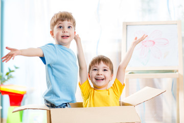 happy kids boys playing and sitting in cardboard box