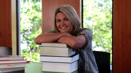 Smiling mature student leaning on pile of books