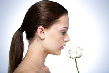 Side view portrait of attractive young woman with flower