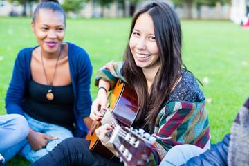 Gitarristin macht Musik mit Freuden im Park