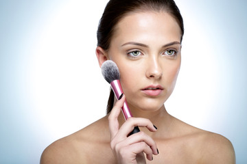 Portrait of a young beautful woman holding cosmetic brush