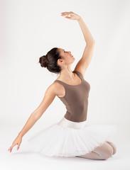 ballet dancer sitting on white studio floor