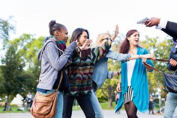 Gruppe Mädchen wird von Räuber mit Waffe bedroht