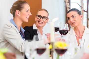Frauen bei Geschäftsessen stoßen an
