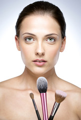 Closeup portrait of a beautiful woman holding brush for makeup